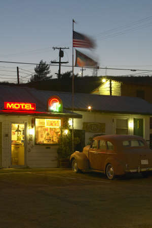 Route 66 neon sign and historic vintage roadside motel welcomes old cars and guests in Barstow California