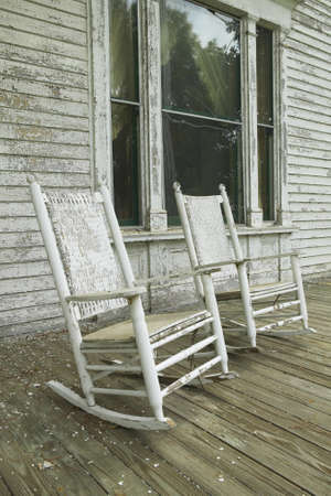 disrepair: Rocking chairs on porch of southern house in disrepair along Highway 22 in Central Georgia Stock Photo