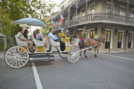 Horse Carriage and tourists in French Quarter of New Orleans, Louisiana