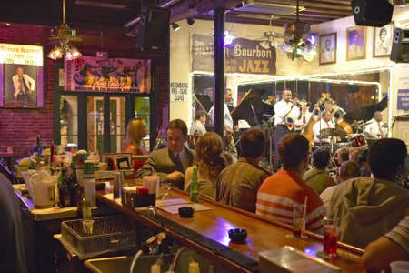 band bar: Maison Bourbon Jazz Club with Dixieland band and trumpet player performing at night behind bar with drinking customers in French Quarter in New Orleans, Louisiana