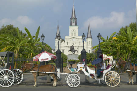 Horse Carriage and tourists in front of Andrew Jackson Statue & St. Louis Cathedral, Jackson Square in New Orleans, Louisiana