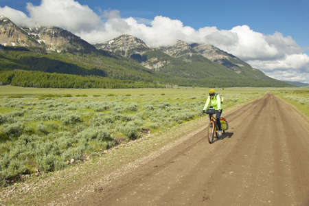 roughing: Bicyclist riding through spring flowers and mountains in Centennial Valley near Lakeview, MT