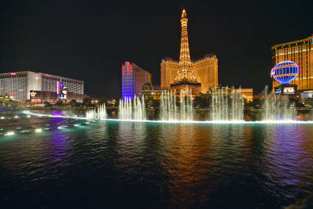 nv: Bellagio Casino Water Show at night with Paris Casino and Eiffel Tower, Las Vegas, NV