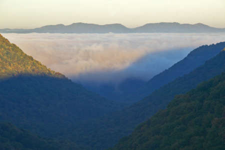 Morning fog at sunrise in autumn mountains of West Virginia in Babcock State Park photo