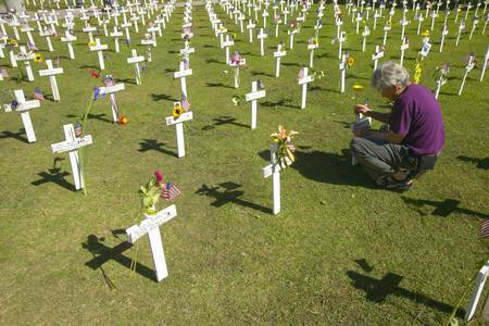 Woman kneels at mock cemetery honoring 1500+ Iraqi servicemen killed in Iraq War, Ventura California