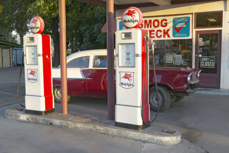 A vintage 1957 Chevy parked in front of antique gas pumps at Ernies old auto garage in Santa Paula, CA
