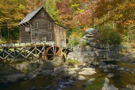 grist: Glade Creek Grist Mil e riflessi d'autunno e d'acqua caduta in Babcock State Park, Virginia Occidentale Editoriali
