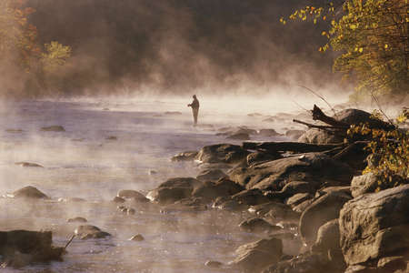 Solitary fly fisherman in morning mist, Housatonic River, Connecticut