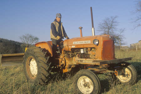 Farmer standing on tractor on cattle farm in Bourbon, MO