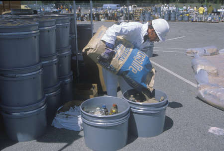A worker pouring the contents of a bag into a container of waste materials at waste cleanup site on Earth Day at the Unocal plant in Wilmington, Los Angeles, CA