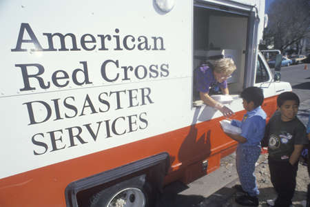A Red Cross worker handing out meals from a disaster services van