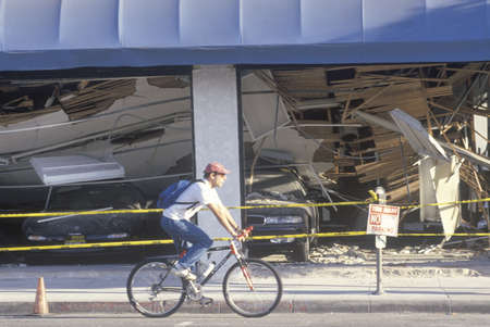 northridge: A cyclist riding past a destroyed car dealership in Santa Monica after the Northridge earthquake in 1994