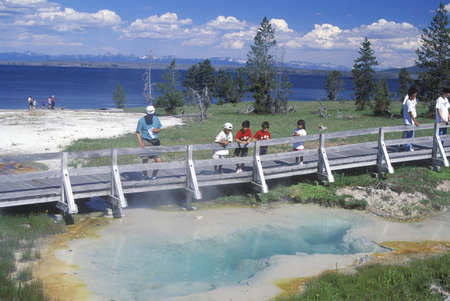 sightseers: Tourists Looking at Geyser, Yellowstone National Park, Wyoming Editorial