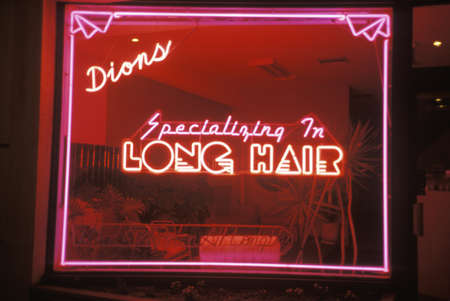 advertise with us: A neon sign that reads Dions, specializing in long hair