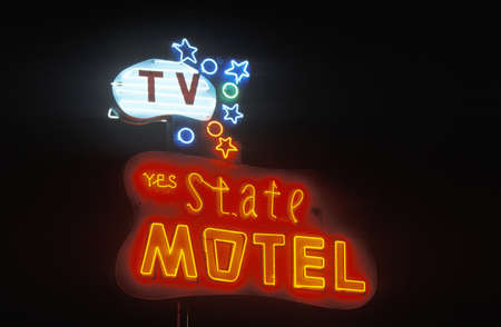 advertise with us: A neon sign that reads State Motel