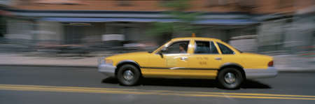briskness: This is a yellow taxi in motion going through Manhattan during the day. The taxi is slightly blurred as is the surrounding scenery.