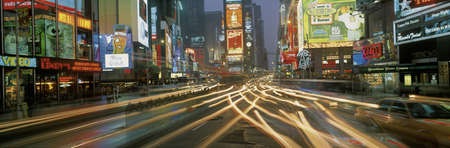 briskness: This is Times Square at night. There are streaked lights from the cars traveling through the square. There are neon lights from the billboards as well as signs. Editorial
