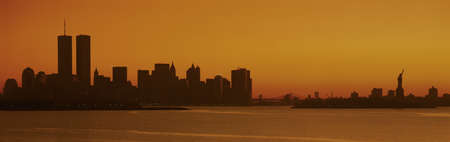 This is the Manhattan skyline from New Jersey. It shows the Statue of Liberty on the right, the world Trade Towers on the left and the skyline in silhouette at sunrise. photo
