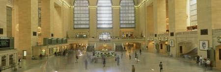 This is the interior of Grand Central Station after its new renovation. There are commuters going to their trains and monitors showing the train times.