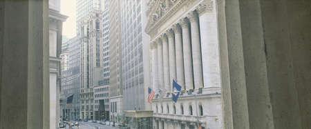 This is a view looking at the exterior of the New York Stock Exchange on Wall Street. It is framed by two white columns.