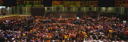 This is the Chicago Board of Trade trading floor. It is where they trade commodity futures such as corn, wheat, and gold. The floor is full of traders and the lighted boards showing prices are at the top of the walls. photo