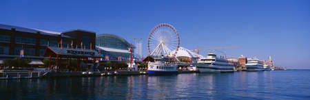 tour boats: This is Navy Pier with its working Ferris wheel and summer tour boats docked next to it in Lake Michigan.