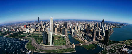 This is an aerial view of the skyline, Lake Michigan and the Chicago Harbor on left during summer.  Boats are moored in the harbor and Lake Shore Drive winds around the city.  photo