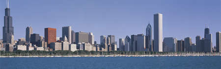 This is the complete Chicago skyline with the Chicago Harbor in the foreground. It is the view from the Adler Planetarium in the morning during summer. The view extends from the Sears Tower on the left to the John Hancock Building on the right. Sailboats  Stock Photo