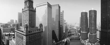 This is a view looking over the Chicago River. The Marina Tower Apartments, the Wrigley Building and the skyline surround the river. It is a black and white shot. Stock Photo