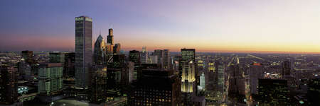 sears: This is an aerial view of the skyline with the Sears Tower at sunset. It is a summer evening and the lights of the city are on.