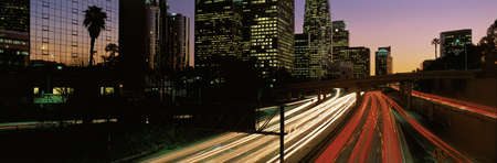 This is the Harbor Freeway with rush hour traffic at sunset. The yellow and red streaked lights from the cars are on the freeway. Stock Photo