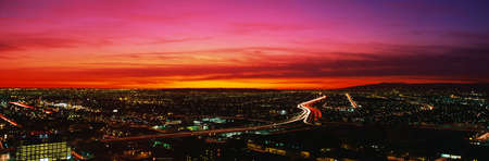 This is an aerial view of downtown Los Angeles at sunset. The streaked lights of the freeway are in the center with an orange sunset sky. photo
