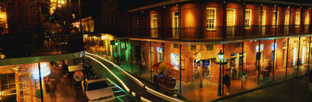 This is Bourbon Street in the French Quarter at night. There are streaked lights from cars and old fashioned gas lamps lining the street. There are balconies with black iron railings on the second floor of the buildings where clubs and restaurants are sit