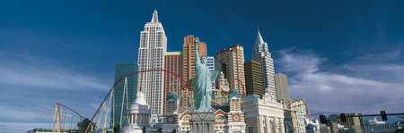 This is the New York, New York Hotel and casino during the day. The buildings show a replica of the Empire State Building, the Chrysler Building, the Statue of Liberty as well as other landmark New York buildings with a large roller coaster weaving in bet