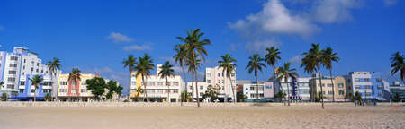 wide: This is the art deco district of South Beach Miami. The buildings are painted in pastel colors surrounded by tropical palm trees. Editorial