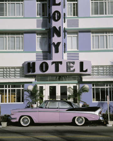 This is the Colony Hotel on the strip of South Beach Miami. There is a purple and black vintage car parked in front of the hotel.
