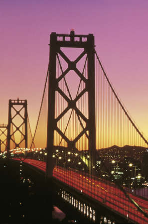 This is the Bay Bridge at sunset. There is a pink and orange glow in the sky. photo