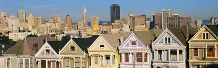 These are the historic Victorian homes in front of the skyline on Steiner Street. They are painted pastel colors and line up next to each other in row house formation. photo