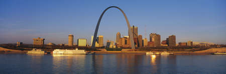 st  louis arch: This is the skyline at sunrise. It is situated along the Mississippi River. There are riverboats on the water with the St. Louis Arch in clear view.