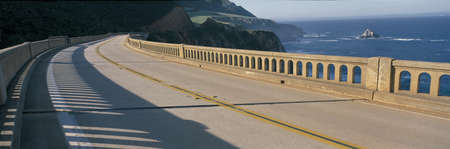 This is the road on the Bixby Bridge. It is Route 1, also known as Pacific Coast Highway. It is next to the mountainous coast and the Pacific Ocean. The road curves around to the right. photo