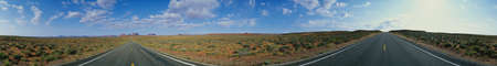 This is a 360 degree image of a fork in the road. The rocks of Monument Valley are small in the background and there is desert foliage on all sides of each road. The sky is blue with white puffy clouds. Stock Photo