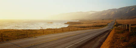 This is Route 1also known as the Pacific Coast Highway. The road is situated next to the ocean with the mountains in the distance. The road goes off into infinity into the sunset. Archivio Fotografico