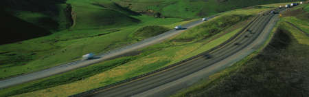 altamont pass: This is Route 580 at the Altamont Pass. There is green grass on each side of the highway with two separate roads for cars to travel in each direction. Stock Photo