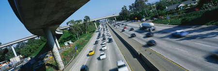 This is the Interstate 405 and 10 at rush hour. There are many cars lined up on the freeway with an overpass on the left hand side. There are a few houses to the right of the freeway.