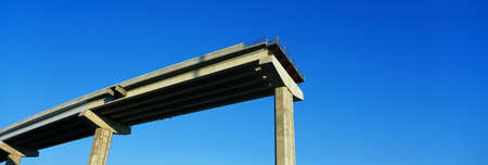 dropoff: This is an unfinished freeway or dead end road. There is a huge drop-off where the road ends. It is supported by concrete pillars that traditionally hold up freeways.