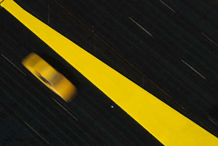 This is a slightly blurred yellow taxi to the left of a yellow dividing line. It is on a drawbridge with black pavement. The dividing line is larger than what is on most roads.