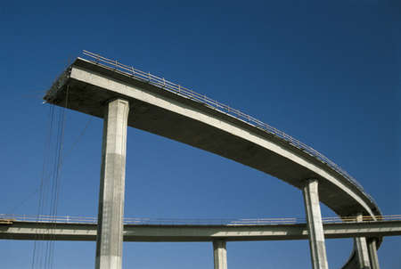 This shows a freeway under construction. It is the end of the road. The upper level of the road curves around and then just completely ends in mid-air.  Stock Photo