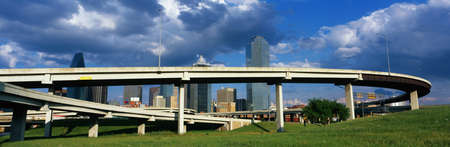 This is a freeway overpass with the Dallas skyline visible behind it. The freeway curves and snakes around in a circle in front of the city. Stock Photo