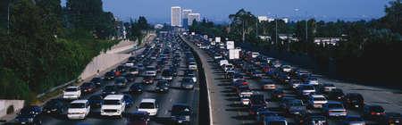 turnpike: Este es hora punta de tr�fico en la autopista 405 al atardecer. Hay 10 carriles de tr�fico total que muestran ambos lados de la autopista. Hay coches parados en cada carril. Editorial