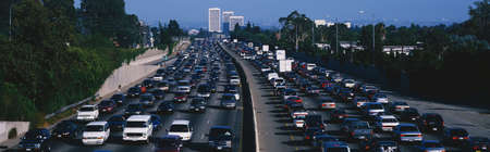 southern california: This is rush hour traffic on the 405 Freeway at sunset. There are 10 lanes of traffic total showing both sides of the freeway. There are cars stopped in every lane.